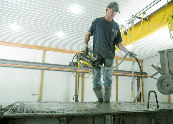Globe/Roger Nomer<br /> Carter Henson spreads concrete on a safe house at Henson Septic and Supplies on Monday.