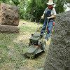 Globe/Roger Nomer<br /> Jim Van Fleet mows over a sunken area at Miller Cemetery on Thursday morning.