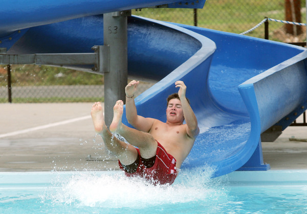 Globe/Roger Nomer<br /> Lifeguard Matt Kersey gets a shock of cold water as he tries out the water slide at Cunningham Pool on Thursday.