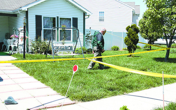 Lebanon Police Det.-Capt. Maurice Hobson searches the front yard at 2110 Crimson Lane, Lebanon, where a man was stabbed Monday afternoon.