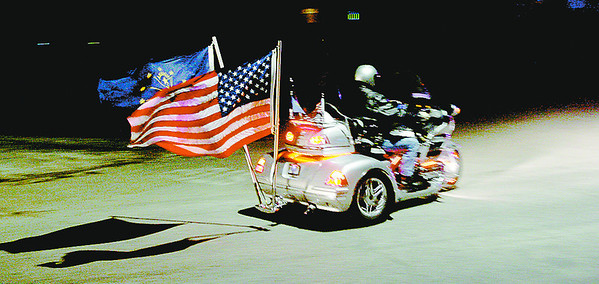 A member of the Gold Wing Riders Assocation passes through the intersection of North East Street and Ulen Drive during the group's parade of lights Saturday night in Lebanon.