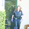 Lebanon Police Officer Amy Dickerson walks toward her cruiser for evidence-gathering material at the scene of a stabbing in Lebanon Monday afternoon; other officers  can be seen through the home's storm door.