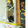 Lebanon firefighter Mark Brown checks the interior of the Magic Mirror salon at 2210 N. Lebanon St. after a car shattered the front window Thursday afternoon.