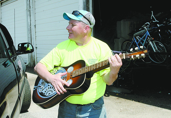 Lonnie Culley picks a tune on a Dobro steel guitar that is one of dozens of items to be sold at the Lebanon Street Department's annual auction Thursday.