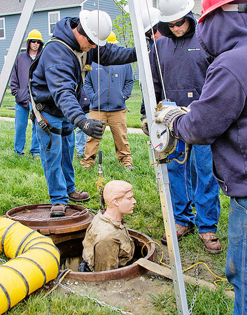 Submitted photo<br /> Linemen from Boone REMC guide a manniquin from a mahole during a confined spaces training program in The Neighborhoods at Anson recently.