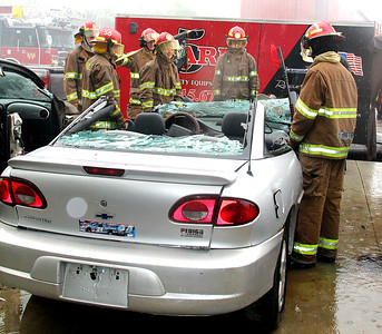 GETTING OUT: Cadets stand around at the extrication station while waiting for their next HERO evolution. 5-Alarm supplied equipment for the cadets to use on a number of cars.