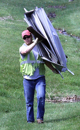 HELPING HAND: A clean-up worker helps remove part of the damaged barn from the west side of S. CR 875 E.