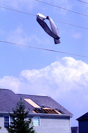 STORM DEBRIS: A piece of tin hangs from power lines while a house with its back facing S. CR 875 E. shows roof damage.
