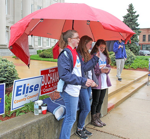 Rod Rose The Lebanon Reporter<br /> COURTHOUSE POLITICS: Sheltered under a big red umbrella, Sutherlin Calhoun (from left), Kenlin Calhoun and Claire Nieshalla greet voters at the Boone County Courthouse at mid-morning Tuesday.