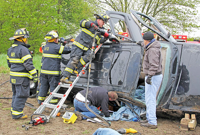 Rod Rose The Lebanon Reporter ACCIDENT INJURIES TWO: An Advance Fire Department firefighter speaks to the entrapped Heather York, 39, Advance, as other firefighters begin to remove the roof of the Ford Explorer in which she was a passenger in a 10:27 a.m. Thursday crash on CR 300 S just east of the Boone-Montgomery county line. Boone County Sheriff's Sgt. Chris Burcham said that the SUV was driven by David Ehirie, 42, Advance, who was west bound on CR 300 S when he lost control on wet pavement in a curve. The SUV slide off the north side of the road, hit a culvert, and rolled over three to four times, Burcham said. York, who was trapped for 20 to 25 minutes, suffered hip and shoulder injuries. Ehirie, who was able to exit the SUV on his own, complained of leg, back and neck pain.