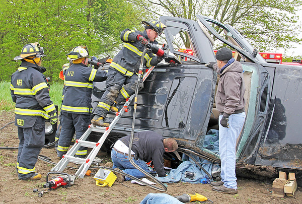 Rod Rose The Lebanon Reporter<br /> ACCIDENT INJURIES TWO: An Advance Fire Department firefighter speaks to the entrapped Heather York, 39, Advance, as other firefighters begin to remove the roof of the Ford Explorer in which she was a passenger in a 10:27 a.m. Thursday crash on CR 300 S just east of the Boone-Montgomery county line. Boone County Sheriff's Sgt. Chris Burcham said that the SUV was driven by David Ehirie, 42, Advance, who was west bound on CR 300 S when he lost control on wet pavement in a curve. The SUV slide off the north side of the road, hit a culvert, and rolled over three to four times, Burcham said. York, who was trapped for 20 to 25 minutes, suffered hip and shoulder injuries. Ehirie, who was able to exit the SUV on his own, complained of leg, back and neck pain.