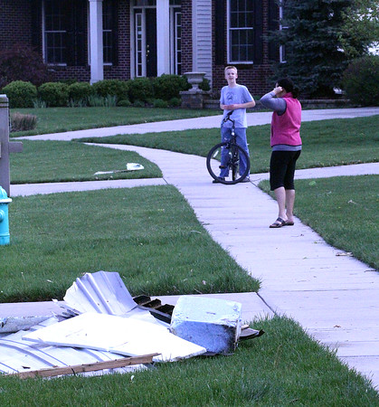 WHAT HAPPENED: A boy on a bike and a woman, neighbors in the Rock Bridge subdivision, talk on the sidewalk in front of some debris.