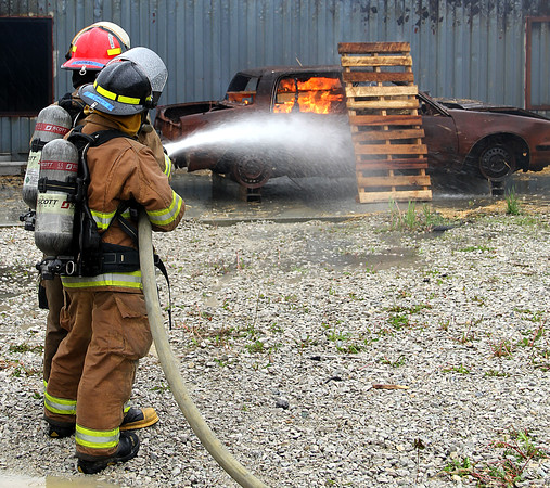 REAL SITUATION: Louisville's Fairdale High School Battalion 17 members Gavin Thomas (front) and Caleigh Toney (rear) work together on the car fire evolution.