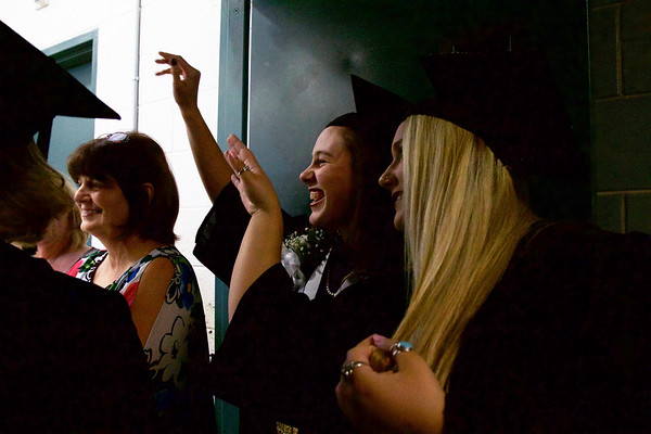 ELODIE REED - FOR THE BERKSHIRE EAGLE Medical assisting graduates Caitlyn Cross, left, and Jaci Tart, right, wave to their families before marching into the McCann Technical School's gymasium during the postsecondary graduation ceremony Thursday night.