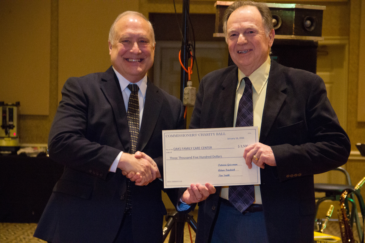 ALEC SMITH / GAZETTE Medina County Commissioner Tim Smith presents a donation to Oaks Family Care Center founder Stanley Barlow at the commissioners' ball held Saturday night at Weymouth Country Club.