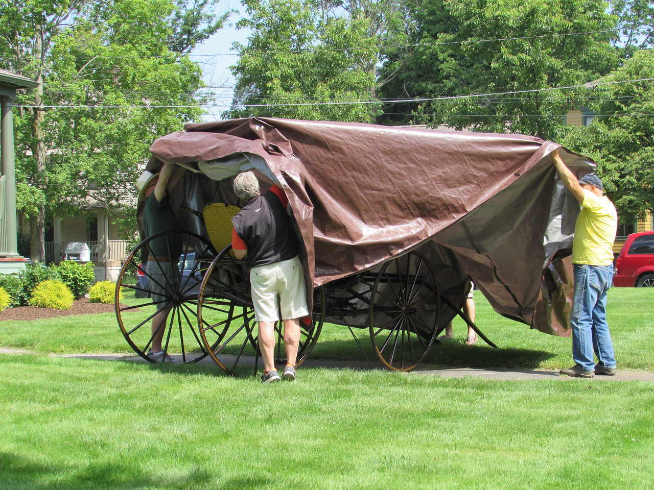 LYDIA MAINZER / SPECIAL TO THE GAZETTE Medina County Historical Society Members pull back a tarp covering a McDowell-Phillips carriage Saturday as it was unveiled to the public after being restored.