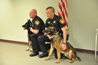 ASHLEY FOX / GAZETTE Deputies Dan Kohler, left, and Dave King, right, kneel with their dogs Apollo and Rocky. Both deputies completed six weeks of training.