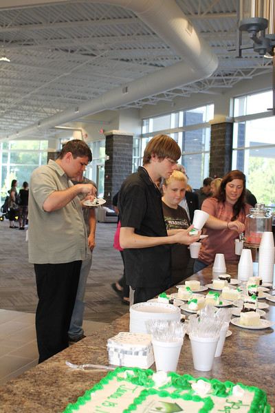 LAWRENCE PANTAGES / GAZETTE People served by the nonprofit Medina Creative Housing agency enjoy 25th birthday cake and refreshments Thursday in a party at Heartland Community Church, 3400 Weymouth Road, Medina Township.
