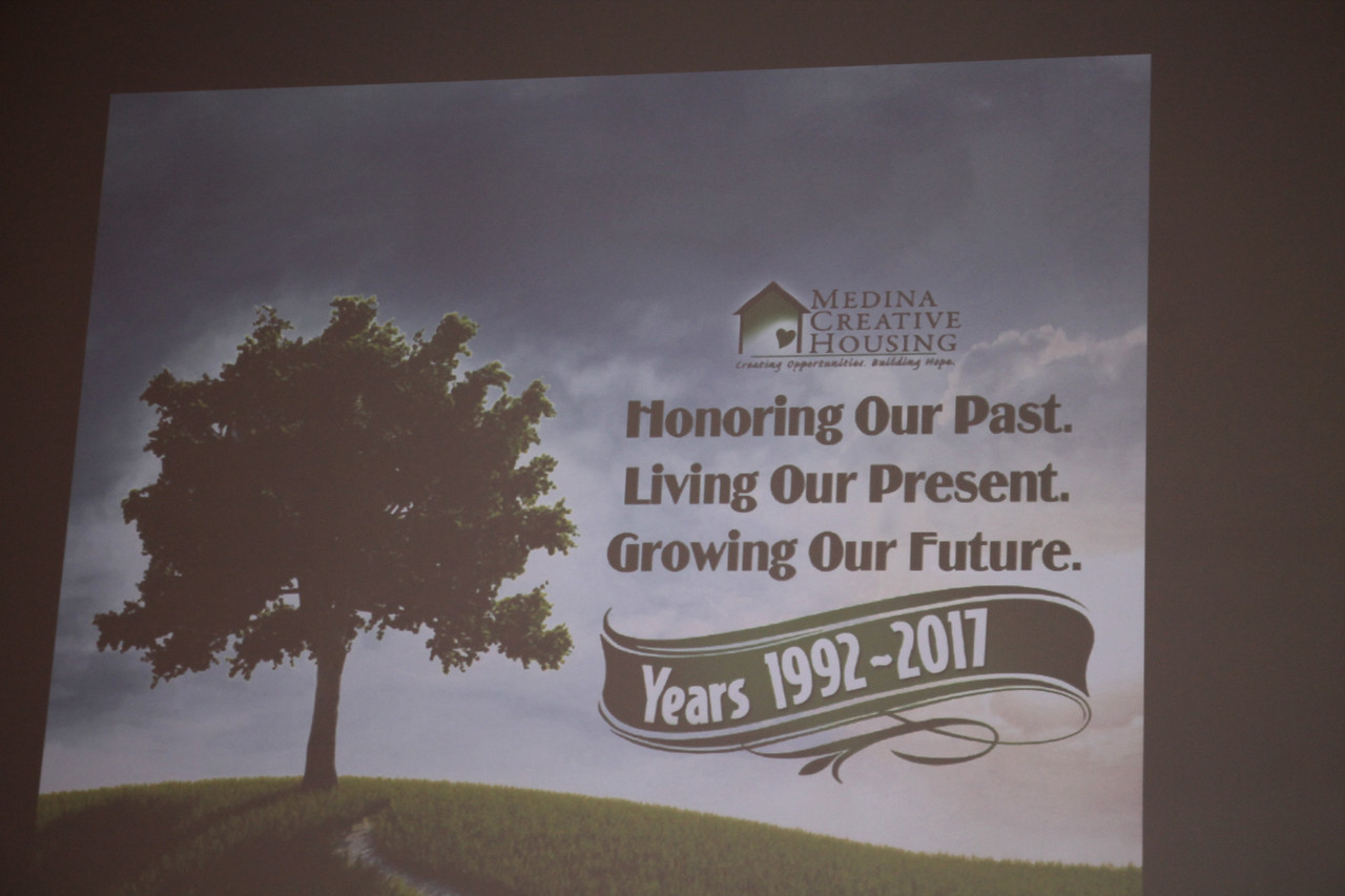 LAWRENCE PANTAGES / GAZETTE The logo of the nonprofit Medina Creative Housing is shown on a big screen during the agency's 25th birthday party last Thursday at Heartland Community Church, 3400 Weymouth Road, Medina Township.