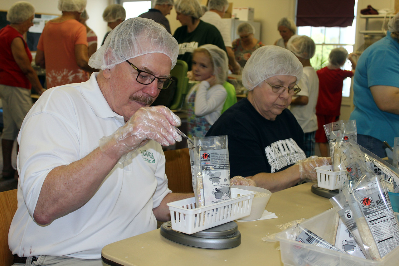 HALEE HEIRONIMUS / GAZETTE Ed Hitcshue, Medina, and Laurel Jordan, Hinckley, weigh the meals and add more rice if needed. Each bag has to weigh between 3.89 to 3.94 grams.
