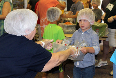"HALEE HEIRONIMUS / GAZETTE Daniel Bell, 4, of Medina serves as a ""runner"" by taking the bagged meals to the packaging station."