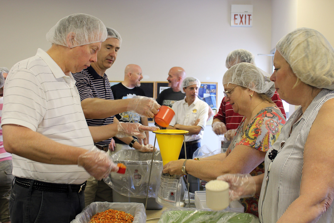 HALEE HEIRONIMUS / GAZETTE Pictured from left: Bryan Conrad, Medina, Steve Michaels, Wadsworth, Cheryl Scott, Medina, and Barb Conrad, Medina, put one cup of rice, one cup of soy protein and about 2 tablespoons of dehydrated vegetables through a funnel to make one packaged meal.