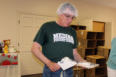 HALEE HEIRONIMUS / GAZETTE The Rev. Henry Pearce puts labels on the packaged meals.