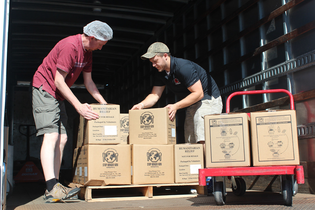 HALEE HEIRONIMUS / GAZETTE Doug Skilskyj, Litchfield, and Andrew Moser, Stop Hunger Now representative from Pittsburg, PA., loads boxes of the packaged food into the truck. Each box holds about 36 bags of packaged food.