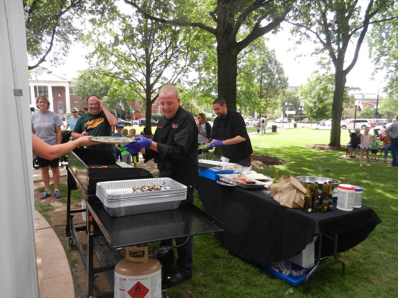 ANNIE RYAN HYRA / SPECIAL TO THE GAZETTE Chef Ryan Marino, owner of The Corkscrew Saloon in Medina, makes flatbread pizzas with all locally sourced ingredients Saturday during the Farmers Market event on Public Square. Chef de cuisine Alan Carroll, who works with Marino, is at right.