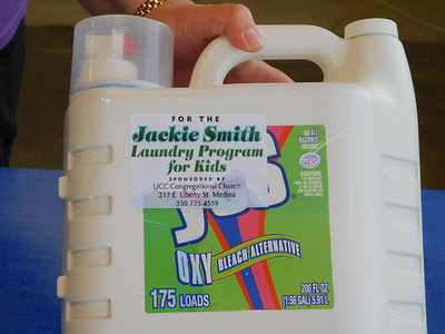BOB FINNAN / GAZETTE An attendant at North Court Laundromat holds up a bottle of detergent in the Jackie Smith Laundry Program for Kids.