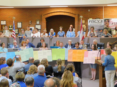 BOB FINNAN / GAZETTE A group of students hold up letters of support for the LGBTQ ordinances Monday night, which was voted upon by City Council.