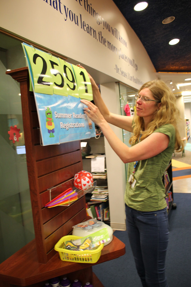 LAWRENCE PANTAGES / GAZETTE Gail Ebey, supervisor of the children's department at the Medina County District Library, changes the numbers on the board to reflect the latest total of participants in the system's Summer Reading Game program.
