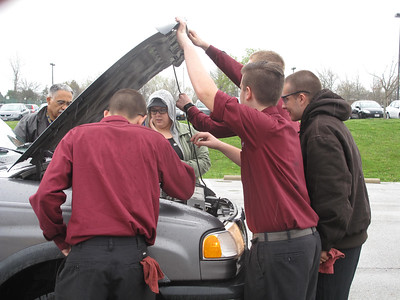 ELIZABETH DOBBINS / GAZETTE Four Medina County Career Center seniors and AAA travel agent Julie Falsone inspect the engine of a truck belonging to Medina High School tenth grade teacher David Johnson.