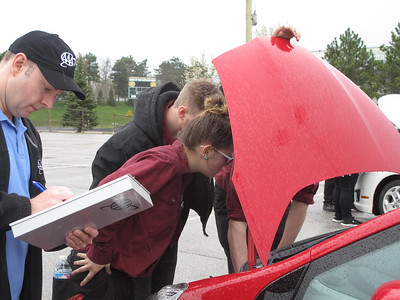 ELIZABETH DOBBINS / GAZETTE Medina County Career Center seniors Destiny Hanzel of Liverpool Township and Brodie Gange of Litchfield Township inspect the engine of a high school student's car. AAA insurance agent Bob Combs writes their findings down on an inspection sheet.