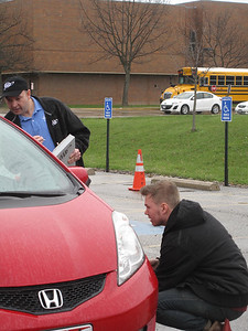 ELIZABETH DOBBINS / GAZETTE Brodie Gange of Litchfield Township, Medina County Career Center senior, checks the tire pressure as insurance agent Bob Combs speaks to the driver.