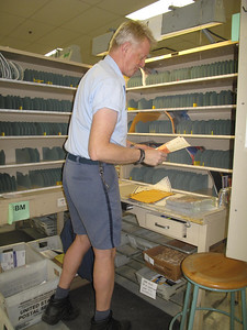 MARINA MALENIC / THE GAZETTE Greg McClure sorts his mail Friday morning to prepare for his Medina Square delivery route.