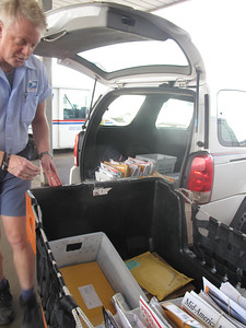 MARINA MALENIC / THE GAZETTE           Greg McClure loads his mail van to prepare for his Friday route on Medina Square.