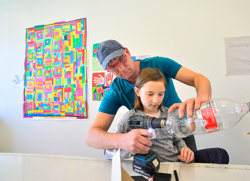 KRISTOPHER RADDER — BRATTLEBORO REFORMER<br /> Walter Hagedorn helps Alex Day by drilling some holes into a bottle that they are transforming into a housing unit for spin art as part of the Mini Spin Art 1000 Upcycle Builder's Workshop at the River Gallery School of Art on Wednesday, April 17, 2019.  Hagedorn is hosting another class on Saturday at 1 p.m. at the River Gallery School of Art.