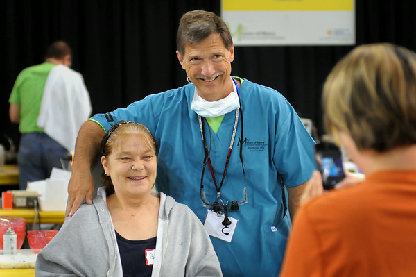 Betty Gronewold of Winnebago and dentist Ken Geiger of Sheboygan, Wis., shows off her new smile for a photograph after he fitted her with a partial on Saturday at the Mission of Mercy. Photo by John Cross