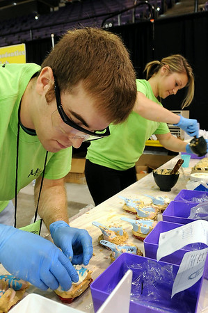 Volunteers Scott Prenger of Minneapolis and Anna Tatarowicz of Hermantown prepare partials for patients at the Mission of Mercy on Saturday. Photo by John Cross