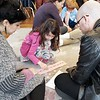 BEN GARVER — THE BERKSHIRE EAGLE<br /> Dulci Squailia, 6, shows her parents Najwa and Gabby, some of her projects at the Montessori School during an open house celebrating the expansion of the campus.