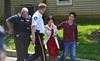 A man and woman who were prevented by police from approaching the scene of a shooting on Harvard Drive in Montgomery Township are escorted from the area.   Monday, June 2, 2014. Photo by Geoff Patton