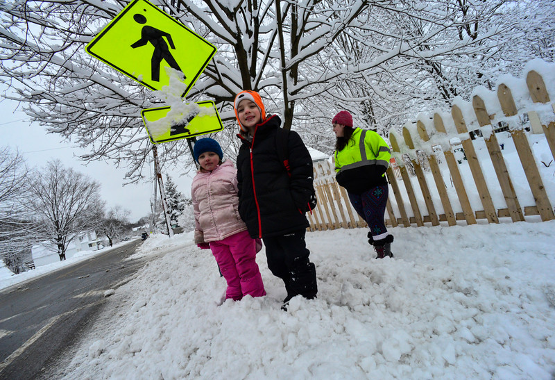 KRISTOPHER RADDER - BRATTLEBORO REFORMER<br /> Samuel, 7, and Lilli McKelvey, 6, wait for their school bus on South Main Street, in Brattleboro, after a 90-minute delay as their mother Samantha Pecor watches them on Thursday, March 8, 2018.