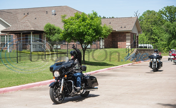 Motorcycles ride in a parade around the building to entertain residents of The Heights, an assisted living community, in Tyler from their windows on Friday, April 10, 2020.