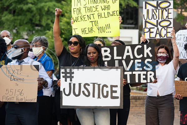 """April Lawson of Tyler holds a sign reading """"#JUSTICE"""" as Ashley Amie, NAACP Tyler Youth Director holds up her first during a press conference held by the NAACP Branch #6232 Tyler to discuss the chapter's position on racial issues on the downtown square in Tyler on Wednesday, June 3, 2020."""