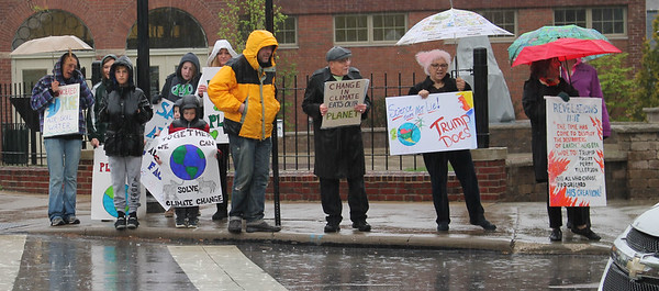LAWRENCE PANTAGES / GAZETTE A group of about 50 protesters gather on separate street corners Saturday during a downpour of rain on Public Square in Medina. The rally, organized by the citizens group Sustainable Medina County, sought to raise awareness of environmental issues.