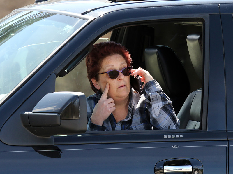 Josephine Peck of Lowell talks to her mother, a resident of Palm Center nursing home in Chelmsford, on the phone from the parking lot, on the day the National Guard was deployed to conduct coronavirus COVID-19 testing after numerous residents tested positive. (SUN/Julia Malakie)