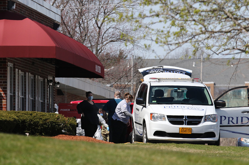 Palm Center nursing home in Chelmsford, where the National Guard was deployed to conduct coronavirus COVID-19 testing after numerous residents tested positive. EMT pushes a woman in a wheelchair into an ambulance as National Guard members disinfect each other and get out of their protective suits. (SUN/Julia Malakie)