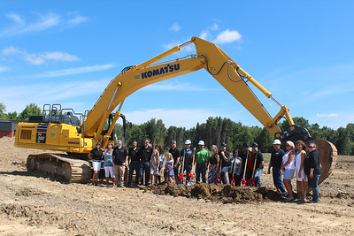 HALEE HEIRONIMUS / GAZETTE Representatives from Pride One Construction, First Merit Bank, Full Spectrum Marketing and the National Carpet Mill Outlet of Medina owners and family celebrate the groundbreaking of the new location, 2255 Medina Rd., Medina, on Monday morning.