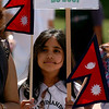 """Sashi Sharma holds a Nepalese flag and a Nepal New Year celebration sign during the parade.<br /> The Nepal New Year of B.S. 2067 was celebrated in Boulder on Sunday with a parade around downtown by area residents.<br /> For more photos, go to  <a href=""""http://www.dailycamera.com"""">http://www.dailycamera.com</a>.<br /> Cliff Grassmick / April 18, 2010"""